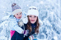 Portrait of a little girl and her mother in winter hat in snow f Royalty Free Stock Photo