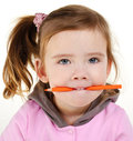 Portrait of little girl holding pencil in teeth Royalty Free Stock Image