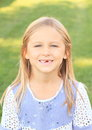 Portrait of little girl with long blond hair soft smile blue eyes and missing tooth Stock Photos