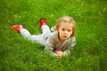 Portrait of little girl lying on green grass Royalty Free Stock Photo