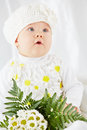Portrait of little girl with open mouth in white clothes who sits on coverlet bunch flowers Stock Photo