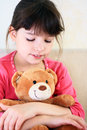 Portrait of a little girl plays with brown teddy bear Stock Photo