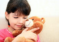 Portrait of a little girl plays with brown teddy bear Royalty Free Stock Photography