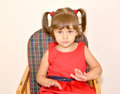 Portrait of the little girl sitting on a children's chair Royalty Free Stock Photo