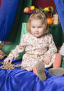 Portrait of a little girl of two years sitting on the bed and fingering the beads the smiles slightly Stock Photography