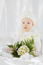 Portrait of little girl in white clothes who sits on white coverlet between pillows with bunch flowers Royalty Free Stock Photography