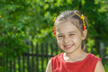 Portrait of little girl young preschool age against green lawn with fence Stock Photos
