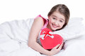 Portrait of little happy girl with a gift lying on the bed isolated on white Stock Images