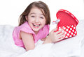 Portrait of little happy girl with a gift lying on the bed isolated on white Royalty Free Stock Photos