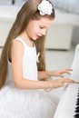 Portrait of little musician in white dress playing piano girl concept music study and creative hobby Royalty Free Stock Image