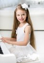 Portrait of little pianist in white dress playing piano girl concept music study and entertainment Stock Photography