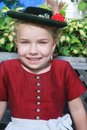 Portrait of a little smiling bavarian girl with hat in traditional dirndl Stock Images