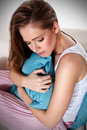Portrait of a lonely beautiful woman hugging a pillow blue Royalty Free Stock Image