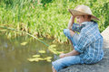 Portrait of looking down on pond water angling boy from grey concrete bridge Royalty Free Stock Images