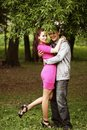 Portrait of love couple embracing outdoor in park looking happy Stock Photos