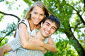 Portrait of love couple embracing outdoor in park looking happy Stock Photo