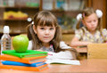 Portrait of lovely girl drawing in copybook and looking at camer Stock Images