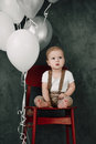 Portrait of lovely little boy happy smiling celebrating 1 year birthday. One year old european boy sitting on floor Royalty Free Stock Photo