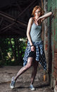 Portrait of lovely young grunge girl in checkered shirt and torn pantyhose Royalty Free Stock Photo