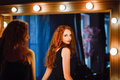 Portrait of lovely young redhead woman looking into mirror the Stock Photo