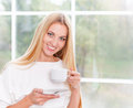 Portrait of lovely young woman having cup of tea at home blond Royalty Free Stock Photo