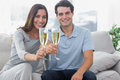 Portrait of lovers toasting their flutes of champagne sat on a couch Royalty Free Stock Photos