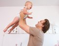 Portrait of a loving father playing with cute baby at home close up Stock Photo