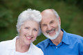 Portrait of a loving senior couple standing together outdoors facing the camera and smiling with their heads touching Royalty Free Stock Photos