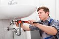 Portrait of male plumber fixing a sink in bathroom Stock Images