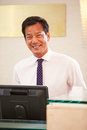 Portrait of male receptionist at hotel front desk Stock Image