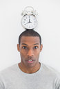 Portrait of a man with an alarm clock on top of his head close up over white background Royalty Free Stock Photo