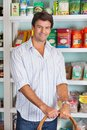 Portrait of man with basket in grocery store handsome mid adult standing against shelves Royalty Free Stock Photography