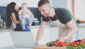 Portrait of man cooking vegetable in the kitchen while looking at a laptop computer on the table Royalty Free Stock Photo