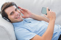 Portrait of a man enjoying music with his smartphone laid on couch Royalty Free Stock Images