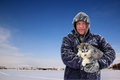 Portrait of a man holding a puppy outdoor in winter Royalty Free Stock Image