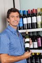 Portrait of man showing alcohol bottle mid adult while standing by shelves at supermarket Royalty Free Stock Images