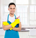 Portrait of man with sprayer ready to do housework in the kitchen Stock Photography