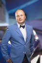 Portrait of a man in suite and bow tie against blurred car background vertical image Stock Photo