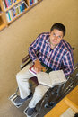Portrait of a man in wheelchair reading a book in library high angle the Stock Photos