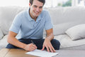 Portrait of a man writing on a paper in the living room Royalty Free Stock Photos