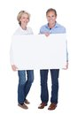 Portrait of mature couple holding placard happy blank isolated over white background Stock Images