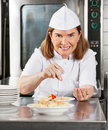 Portrait mature female chef adding spices to dish commercial kitchen counter Stock Image