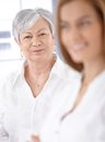Portrait of mature lady smiling young women standing at background Stock Image