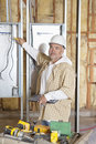 Portrait of a mature male construction worker checking electric meters at construction site Royalty Free Stock Image
