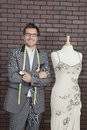 Portrait of mature male fashion designer standing next to tailor s dummy Royalty Free Stock Photo
