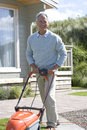 Portrait of mature man mowing in garden Royalty Free Stock Photo