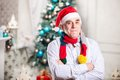 Portrait of mature man in santa s hat and bright scarf standing with arms crossed over christmas background Stock Image