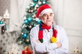 Portrait of mature man in santa s hat and bright scarf standing with arms crossed over christmas background Royalty Free Stock Photography