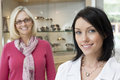 Portrait of a mid adult optician with happy female customer in store Royalty Free Stock Photography