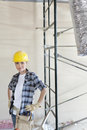 Portrait of mid adult woman standing with hands on hips at construction site Stock Image